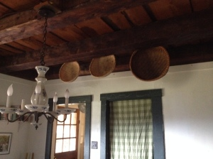 Harvest baskets hang in the kitchen.  The ceiling of the kitchen is the floor of the bedrooms - there is no gap in between.